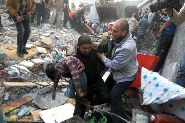 """גופתו של אחד מילדי משפחת אל-דאלו מפונה מביתה שהופגז ב-18 לנובמבר, 2012. 5 ילדים ו-5 נשים נהרגו בהפגזה, שהפרקליט הצבאי הראשי סיכם במלים: """"ננקטו צעדי זהירות שונים כדי לצמצם את הסיכון לפגיעה האגבית בחפים מפשע."""" צילום: אי-אף-פי"""