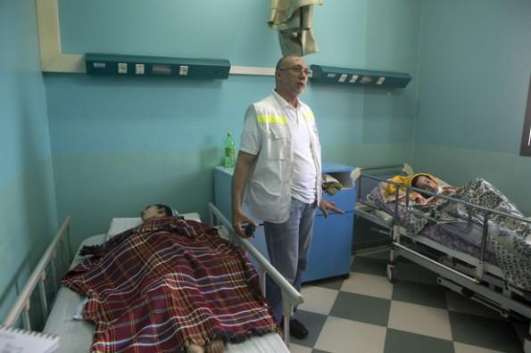 """מנהל """"אל-ופאא"""", בסמאן עלאשי, לצד שני חולים משותקים, 15.7.2014.  צילום: אן פאק"""