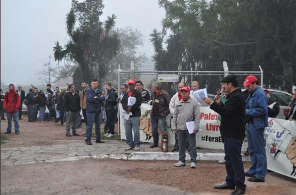 """מפגינים מחוץ למפעל AEL, בבעלות """"אלביט"""", בעיר פורטו אלגרה, קוראים """"לסלק את 'אלביט' מברזיל"""" (מאי 2014)."""